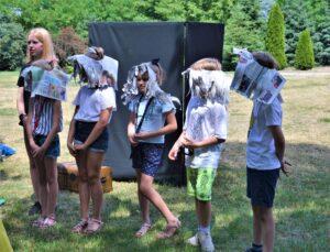 Pora letnia. Kilkoro dzieci stoi w szeregu. Na głowach mają czapki zrobione z gazety.