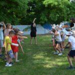Grupa dzieci ustaweiona w dwóch szeregach naprzeciw siebie. Nasladują instruktorkę, która pokazuje gestami ruch traby słonia.