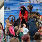 Na scenie mężczyzna przebrany za pirata. Scenografia przedstawia statek piracki na morzy. Przed sceną dzieci ogldające spektakl.