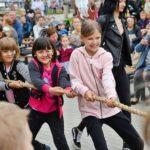 Dzieci bawiące się w przeciąganie liny. Śmiejąsię, są zadowlone z zabawy.