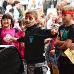 Grupa dzieci przed sceną. Niektóre mają pomalowane buziew pirackie makijaże. Są roześmiane.
