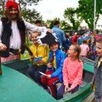 Troje dzieci siedzi w łodzi. Są uśmiechnęte. Obok toi mężczyzna ubrany w strój pirata. Także się uśmiecha.