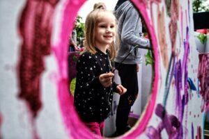 Kilkuletnia dziewczynkatrzma pędzelek w dłoni. Jest radosna.
