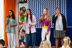 Cztery nastoletnie dziewczyki stoją na scenie. śpiewają do mikrofonów.