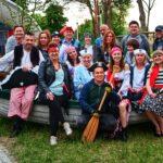 Kilkanaście osób siedzi w łodzi rybackiej. Ubrani są w stroje żeglarzy i piratów.