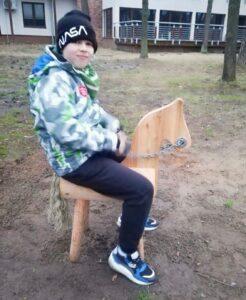 Kilkuletni chłopiec siedzi na drewnianym koniu. Ubrany jest w kolorową kurtkę. Na głowie ma czapkę. Patrzy w prawo.