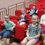 Grupa dzieci siedzi w fotelach kinowych. Patrzą przed siebie, uśmiechają się.