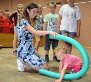 """Młoda kobieta w kolorowej sukience przykuca na podłodze. W ręce trzyma """"makaron"""" do nauki pływania, pod którym przechodzą dzieci."""
