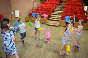 Kilkoro dzieci tańczy z kolorowymi pomponami na sali widdowiskowej.