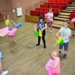 Dzieci tańczące na sali widowiskowej. W rękach trzymają kolorowe pompony do tańca.