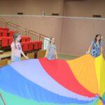 Dzieci bawiące się chustą animacyjną w tęczowych barwach.