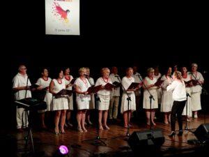 Chór mieszany na scenie podczas występów. Wszyscy ubrani są na biało, śpiewają.