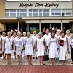 Grupa osób ubranych naa biało stoi przed MiejskimDomem Kultury w Opocznie. Niektórzy lekko się uśmiechają.