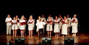 Chór w trakcie występu na scenie. Wszyscy ubrani są na biało. Wrękach trzymają podkładki z nutami. tyłem stoi dyrygentka.