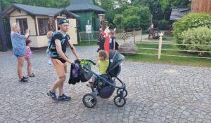 Młody mężczyna pchający przed sobą wózek dziecięcy. Na plecach ma młodsze dziecko w chuście do noszenia.