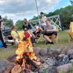 Grupa osób siedząca przy ognisku.