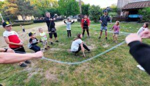 Grupa osób złożona z dzieci i rodziców. Wspólnie się bawią.