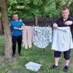 Mężczyzna wieszający pranie na sznurku rozpiętym między dzewami.