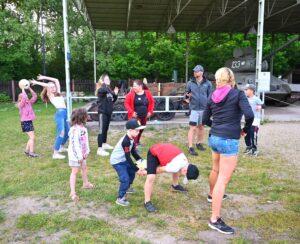 Grupa osób ustawiona w dwa rzędy. Podają sobie piłki.