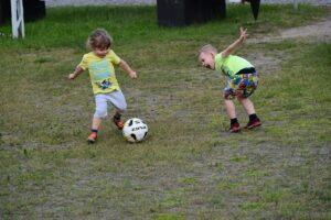 Dwóch małych chłopców kopiących piłkę.