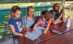 Mężczyna i kobieta z dwójką dzieci - chłopcem i dziewczynką. Siedzą przy stole, na którym leżą kartki papieru. Coś pisza. Kobieta lekko się uśmiecha.