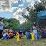 Grupa osób. Część siedzi na leżakach, inne przykucają na trawie. Na pierwszym planie roczna dziewczynka stoi przy żółtym pachołku.