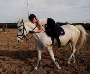Nastoletnia dziewczyna na koniu. Przytula się do jego karku. Koń jest jasnej maści.
