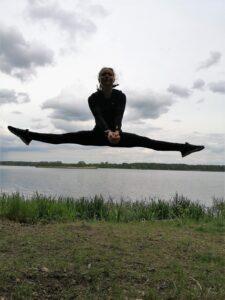 Dziewczyna w pozycji szpagatu zawieszona w powietrzu. W tle jezioro.