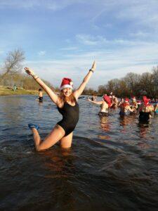 Dziewczyna w kostiumie kąpielowym stoi w rzece. Na głwoei ma czapkę mikołaja. Ręce ma uniesione w górę w geście radości.