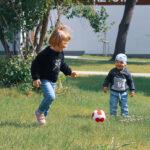 Małe dzieci grają na trawniku w piłkę.