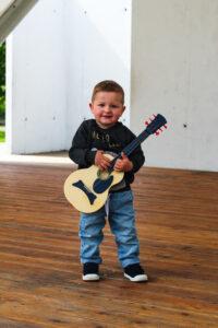 Mały chłopczy z gitarą w ręce. Paatrzy na wprost, lekko się uśmiecha.