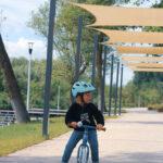 Kilkuletnia dziewczynka na rowerze. Na głowie ma niebieski kask