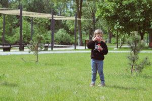 Dziewcznka o jasnych włosach stoi na trawie. Ubrana w czarną bluzę i niebieskie spodnie. Puszcza bńki mydlane.