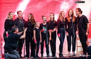 Grupa młodzieży śpiewa do mikrofonów.