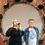 Kobieta i mężczyzna stojący na scenie. W tle mają duże jasne koło i ceglany mur.