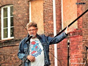 Mężczyzna w średnim wieku. Nosi okulary. Stoi przy mikrofonie, do którego coćś mówi. Ręką wskazuje na mur starego budynku czerwonej cegły.