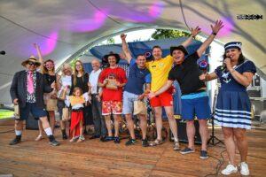 Grupa osób w różnym wieku i płci stoi na scenie. Uśmiechają się i podnoszą ręce do góry w geście radości.