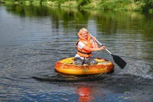 Kobieta siedzi na dużej oponie w kształcie pizzy an środku rzeki. W ręce ma wiosło w kształcie łopaty do pizzy. Ubrana jest w pomarańczowy kapok.