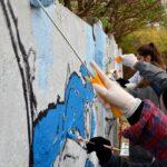 Fragment betonowego ogrodzenia. Grupa młodych ludzi maluje na nim mural.