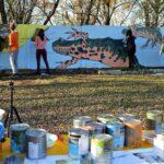 Na pierwszym planie rzą puszek z farbami. W oddali betonowy mur, na którym grupa młodziezy maluje graffiti.