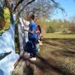 Fragment betonowego ogrodzenia. Kilka osób maluje na nim mural.