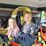 Czworo dzieci siedzi w kabinie samochodu strażackiego.