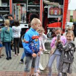 Grupa dzieci stoi przy samochodzie strażackim