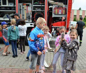 Grupa dzieci stoi przed wozem strażackim. Kilkoro z nich trzyma wąż do gaszenia pożarów. Dzieci są uśmiechnięte.