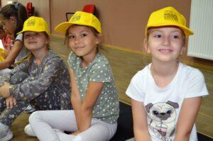 Trzy dziewczynki siedzą na podłodze. Na głowach mają żółte czapki z daszkiem. Patrzą w kamerę i uśmiechają się.
