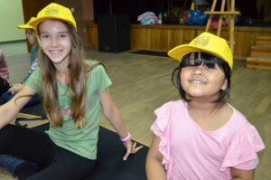Dwie dziewczynki siedza na p[odłodze. Na głowach mają żółte czapki z daszkiem. Uśmiechają się