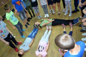 Troje dzieci leży na podłodze, inne stoją wokół nich