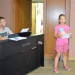 Mężczyna siedzi przy pianinie. Obok stoi dziewcznka, śpiewa