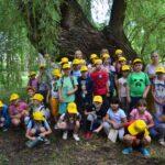 Grupa dzieci pozuje do zdjęcia. Na głowach mają żółte czapki z daszkiem. W tle drzewa okryte zielonym liśćmi.
