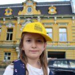 Dziewczynka w żółtej czapce z daszkiem. W tle zabytkowa kamienica